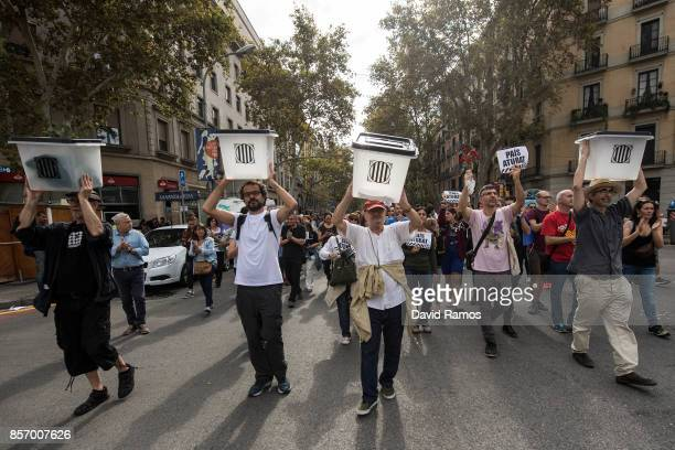 Citizens hold up ballot boxes as they march towards a school which acted as polling station in the referendum and was subsequently raided during a...