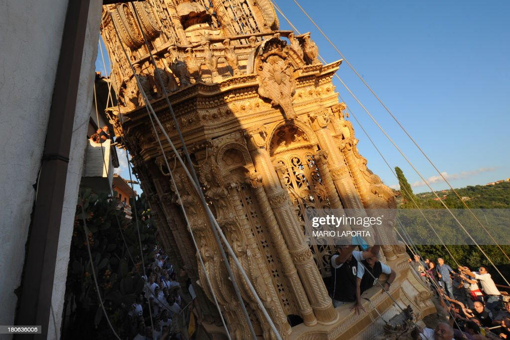 Citizens keep a rope to balance a 25 meters wheat obelisk build in honor of Madonna Addolorata (Our Lady Of Sorrows) during a farmer festival in Mirabella Eclano, south of Italy on September 14, 2013. The ancient farmer festival (Medium Eve) after 900 years of stop, restart in XVI age to protect the hard work of farmers like religious festival in honour of the Lady Of Sorrows. 12 Oxen carry the obelisk and all the Mirabella Eclano citizens pull the ropes to balance the obelisk during the slow run.