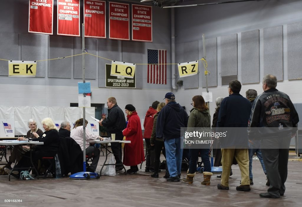 Citizens line up to vote at Belmont High School February 9, 2016 in Belmont, New Hampshire. Voting began in New Hampshire on February 9 in the first US presidential primary, where Donald Trump leads the packed Republican field and Bernie Sanders was polling ahead of Hillary Clinton. Despite its small size New Hampshire's spot on the electoral calendar gives it special importance in the long state-by-state battle to select the Republican and Democratic candidates who will go head to head for the White House. / AFP / Don EMMERT