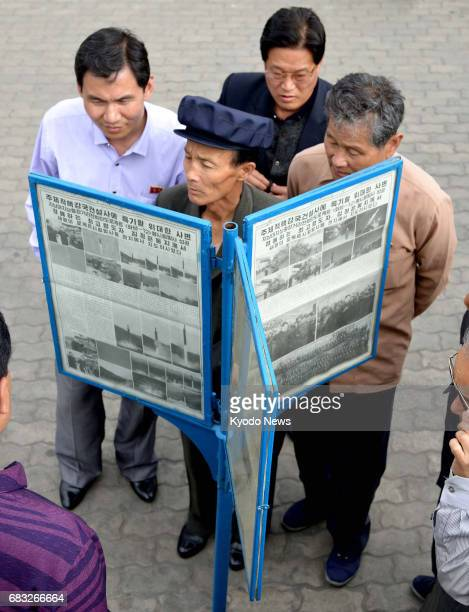 Citizens of Pyongyang look at the Rodong Sinmun newspaper on May 15 2017 The leading newspaper of North Korea reported that the country successfully...