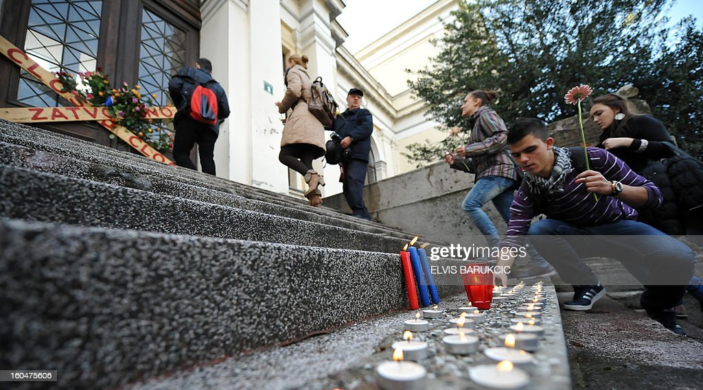 Citizens of Sarajevo leave the National Museum in Sarajevo, on February 1, 2013, after lighting candles and leaving flowers at the door. On the anniversary of it's opening to the public, citizens used the opportunity to protest against neglect of state institutions towards the museum. Bosnia's 125 year old National Museum was closed, 3 months ago, after numerous disputes over its funding that is supposed to be organized by the government of the state.