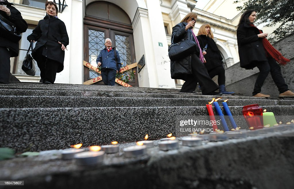 Citizens of Sarajevo leave the National Museum in Sarajevo, on February 1, 2013, after lighting candles and leaving flowers at the door. On the anniversary of it's opening to the public, citizens used the opportunity to protest against neglect of state institutions towards the museum. Bosnia's 125 year old National Museum was closed, 3 months ago, after numerous disputes over its funding that is supposed to be organized by the government of the state. AFP PHOTO/ ELVIS BARUKCIC