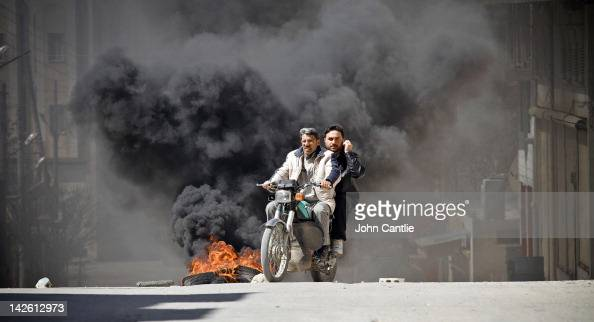 Citizens of Saraquib City flee the town on motorcycle while car tyres burn to reduce the visibility for tank gunners on April 9 2012 in Syria...