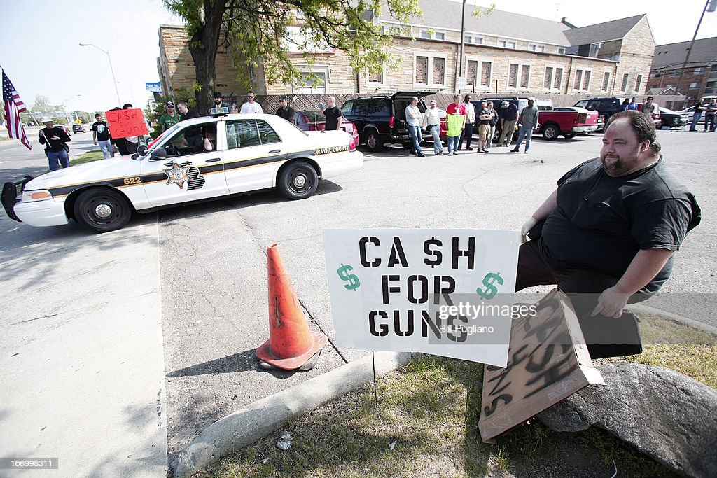 Citizens offering cash for guns wait near the location of a 'Groceries For Guns' gun buyback program May 18, 2013 at the New St. Paul Tabernacle Church of God in Christ in Detroit, Michigan. The event was sponsored by the law firm Goodman Acker P.C. in a public-private partnership with Wayne County. People who brought in guns received a $50 Meijer gift card for each gun.
