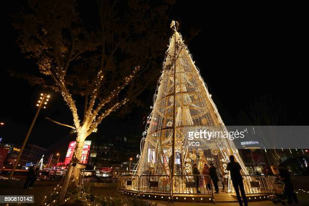 Citizens pose with a 22metrehigh Christmas tree decorated with golden LEDs to welcome Christmas at Qibao Ancient Town on December 11 2017 in Shanghai...