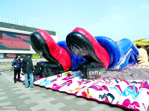Citizens visit a 'inflatable doll' at Wanda Plaza on April 9 2015 in Nanjing Jiangsu province of China The giant inflatable doll which is an...