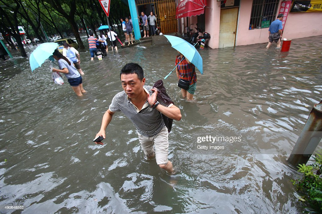 Citizens walk in ponding brought by the typhoon Dujuan on September 30 2015 in Ningbo Zhejiang Province of China Typhoon Dujuan made landfall in the...