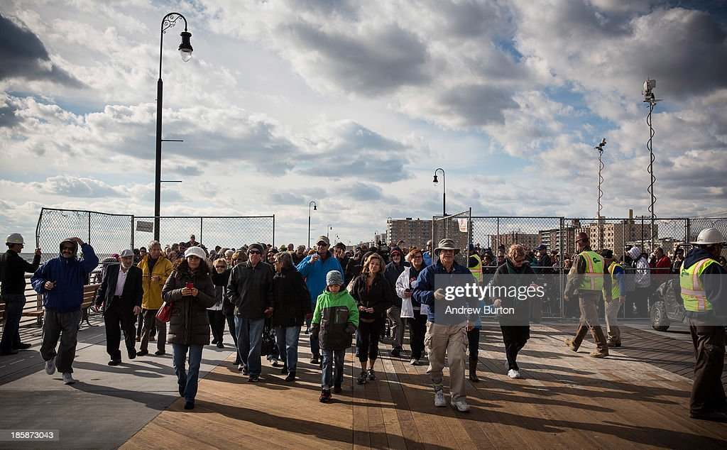 Citizens walk onto the boardwalk during a ceremony to officially reopen the boardwalk on October 25, 2013 in Long Beach, New York. The boardwalk was severely damaged by Superstorm Sandy last year, which killed 285 people and caused billions of dollars in damage. Long Beach's new boardwalk is made of Brazilian hardwood and is estimated to have a lifespan of 30-40 year; the previous boardwalk was only scheduled to last three to seven years.