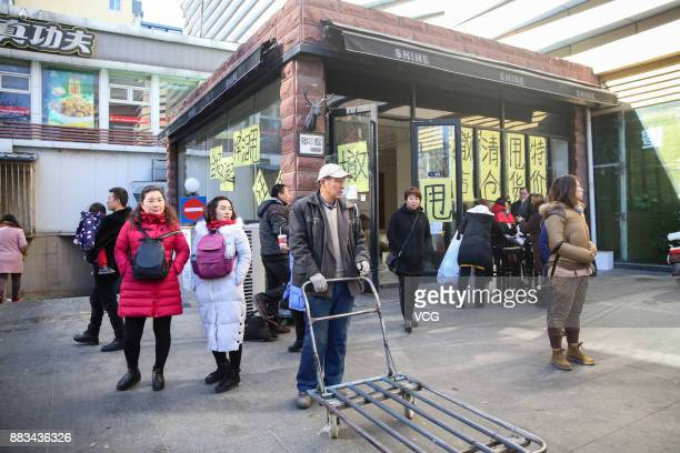 Citizens walk past a shop of Dongding wholesale market before its closing on November 30 2017 in Beijing China The Dongding market the last of 12...