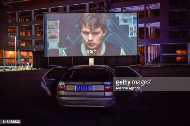 Citizens watch a giant screen movie in their car at a drivein theater on September 13 2017 in Wuhan China A drivein theater or drivein cinema is a...