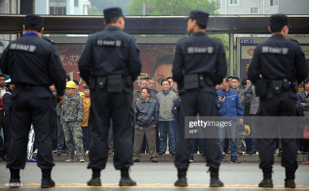 Citizens watch as police stand guard outside the Xianning Intermediate People's Court where Chinese mining tycoon Liu Han stands trial in Xianning, central China's Hubei province on March 31, 2014. Liu Han, who once mounted a billion-dollar bid for an Australian company, went on trial for murder with 35 other alleged gang members, state media reported. The gang, based in Sichuan province in the southwest, are the biggest such 'mafia-style' group to face a courtroom in recent years, Xinhua said. CHINA
