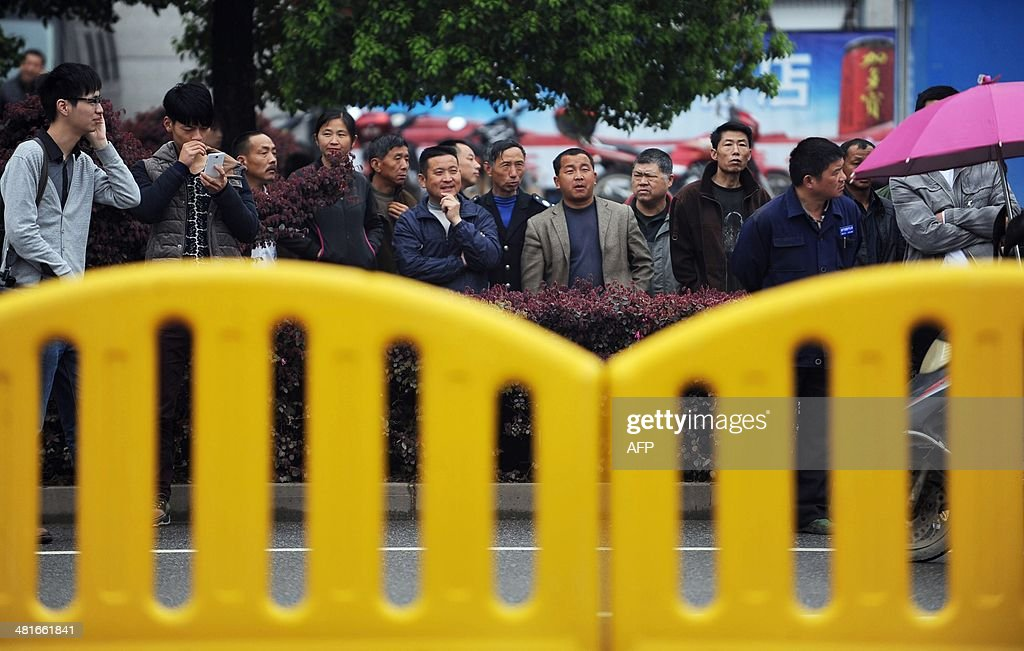 Citizens watch outside the Xianning Intermediate People's Court where Chinese mining tycoon Liu Han stands trial in Xianning, central China's Hubei province on March 31, 2014. Liu Han, who once mounted a billion-dollar bid for an Australian company, went on trial for murder with 35 other alleged gang members, state media reported. The gang, based in Sichuan province in the southwest, are the biggest such 'mafia-style' group to face a courtroom in recent years, Xinhua said. CHINA