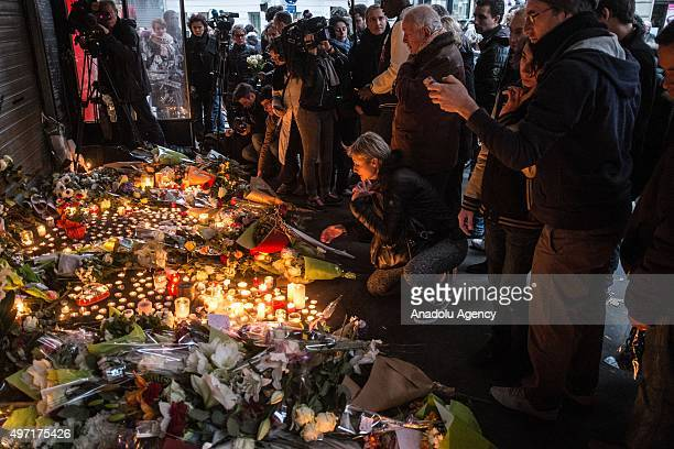 Citizens who gathered around 'La Belle Equipe' leave flowers and light candles in front of the restaurant in Paris France on November 14 2015...