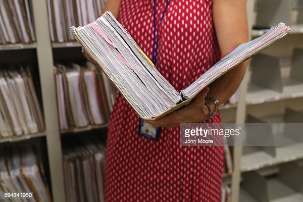 S Citizenship and Immigration Services officer handles a binder with documents supporting a single immigrant's permanent residency application at the...