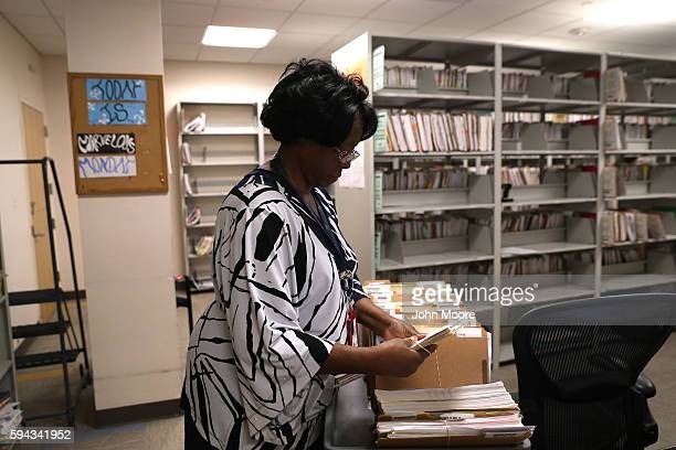 S Citizenship and Immigration Services officer handles folders with immigrants' applications for permanent US residency at the Dallas Field Office on...