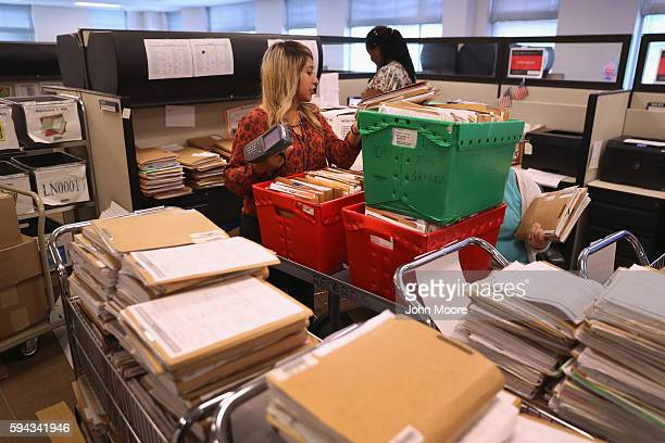 S Citizenship and Immigration Services workers handle folders with immigrants' applications for permanent US residency at the Dallas Field Office on...