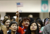 S citizenship candidates celebrate as they wave the US flag after taking the oath of citizenship at a naturalization ceremony at the Los Angeles...