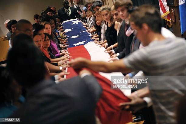 US citizenship candidates fold a US flag during a naturalization ceremony June 14 2012 at the Maryland Historical Society in Baltimore Maryland AFP...