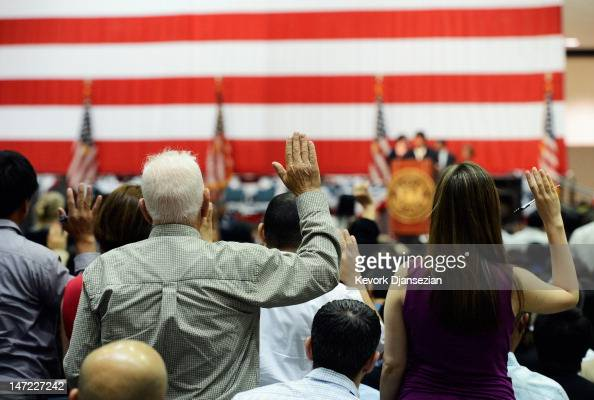 S citizenship candidates raise their arm as they take the oath to apply for a US passort during a naturalization ceremony at the Los Angeles...