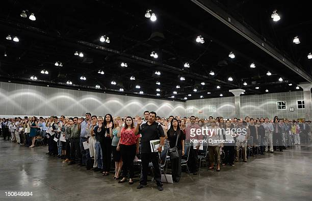 S citizenship candidates take the oath of citizenship at a naturalization ceremony at the Los Angeles Convention Center on August 23 2012 in Los...