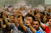 S citizenship candidates waves US flags after taking the oath of citizenship at a naturalization ceremony at the Los Angeles Convention Center on...