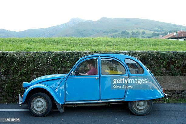 Citroen 2CV driving country road.