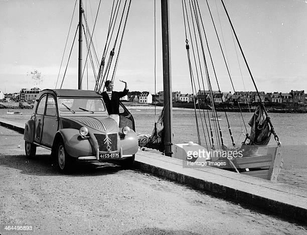 A Citroën 2CV on the quay at a harbour c1957