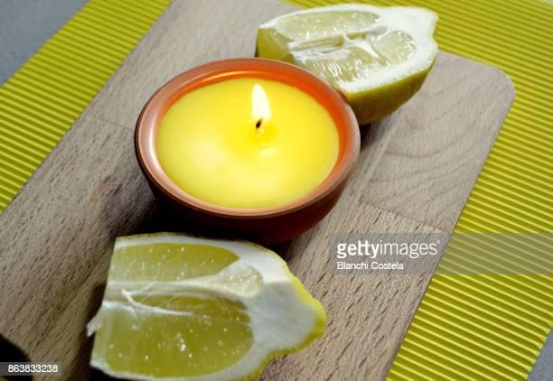 Citronella candle lit and lemon fruit