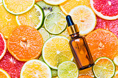 Citrus fruit essential oil bottle with dropper or vitamin c organic cosmetic on citrus background top view.
