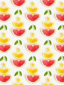 Overhead view citrus fruit slice pattern on white background.