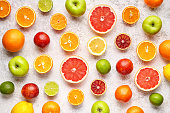 Organic fruit food background. Citrus pattern on white concrete table. Healthy eating and diet. Antioxidant, detox, dieting, clean eating, vegetarian, vegan, fitness or healthy lifestyle concept