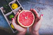 Woman holding a grapefruit