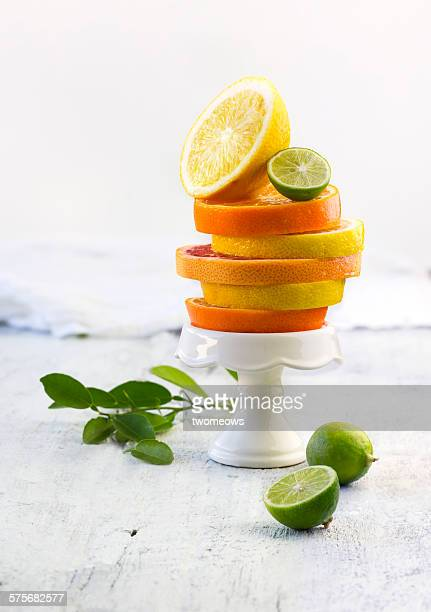 Citrus fruits sliced and stacked on cupcake stand.