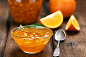 Orange jam on wooden table, focus on jam in bowl, shallow depth of field