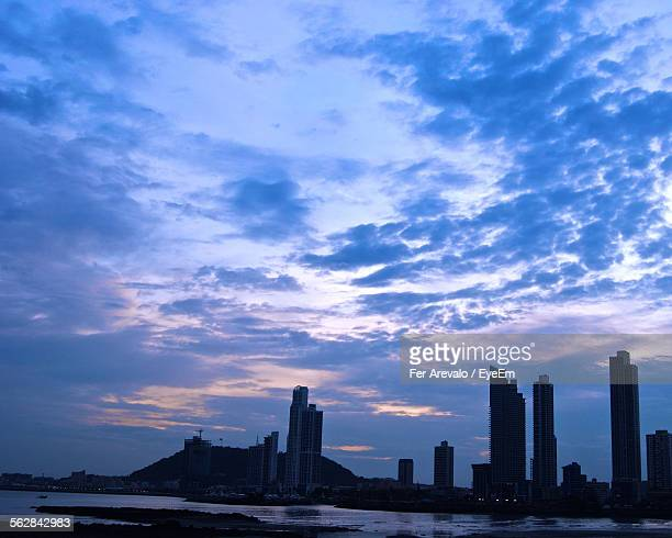 City At Waterfront Against Cloudy Sky During Dusk