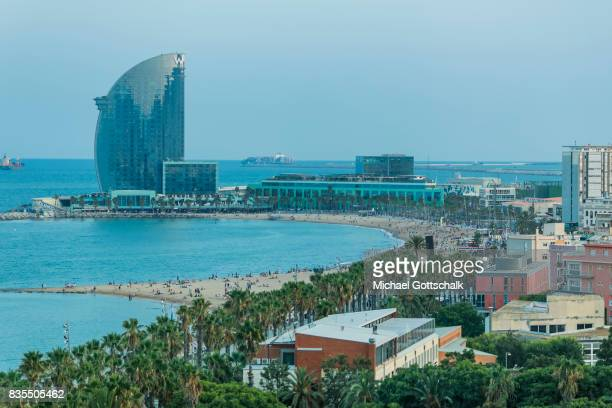 City beach of Barcelona La Barceloneta with palm trees and La Vela building by architect Ricard Bofill on August 18 2017 in Barcelona Spain