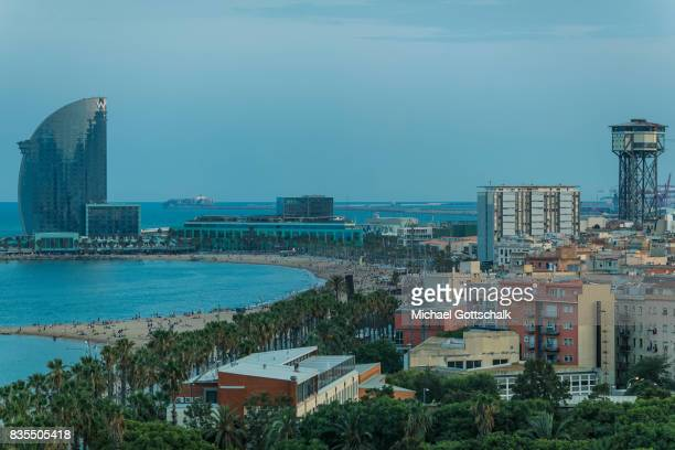 City beach of Barcelona La Barceloneta with palm trees funicular and La Vela building by architect Ricard Bofill on August 18 2017 in Barcelona Spain