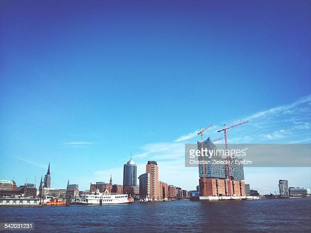 City Buildings And Harbor By River Against Blue Sky
