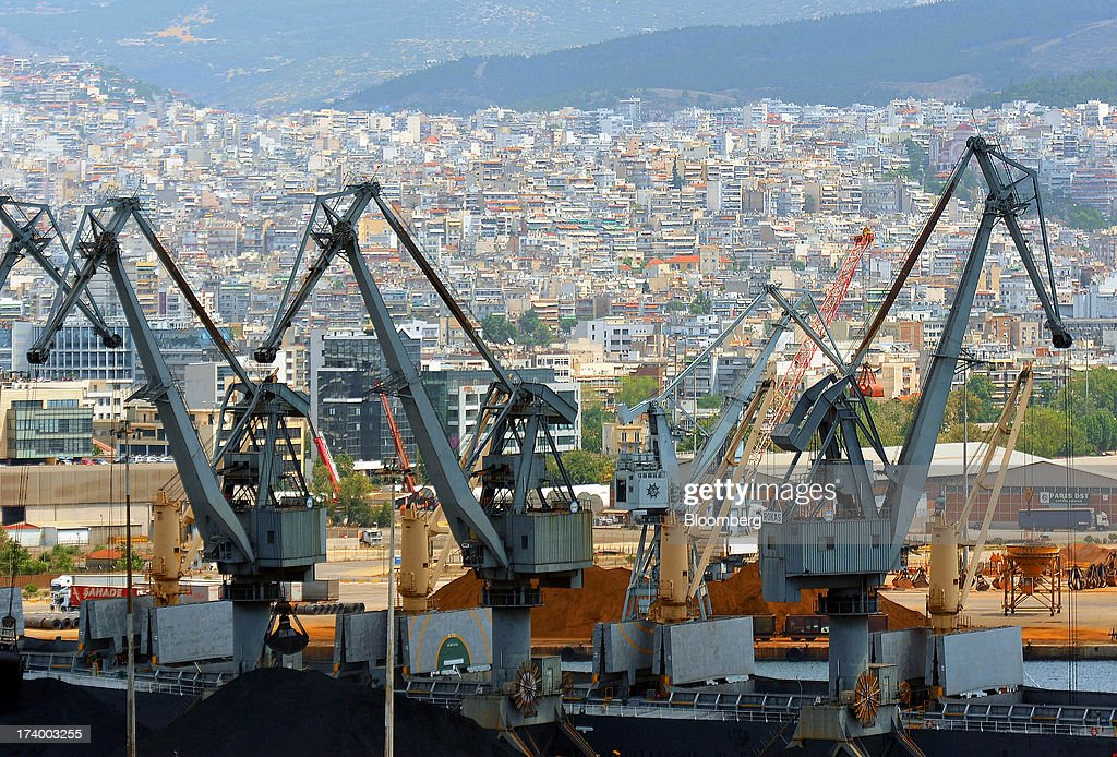 City buildings stand on the skyline beyond dockside cranes operating in the commercial container area of Thessaloniki Port, operated by Thessaloniki Port Authority SA, in Thessaloniki, Greece, on Thursday, July 18, 2013. Russian Railways is interested in buying Thessaloniki Port and Greek rail operator Trainose SA as one single unit, newspaper Real News reported, citing an interview with the Russian company's CEO Vladimir Yakunin. Photographer: Oliver Bunic/Bloomberg via Getty Images