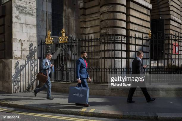 City Businessmen and sunlit railings of St Mary Woolnoth church on Lombard Street on 10th May 2017 in the City of London England St Mary Woolnoth is...