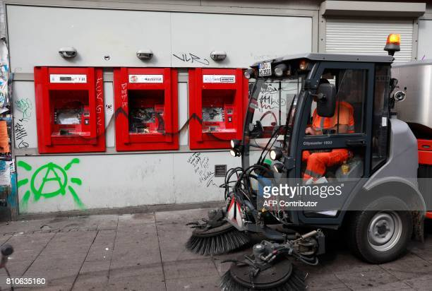 A city cleaner in a sweeper drives past destroyed cash machines after riots in Hamburg's Schanzenviertel district on July 8 2017 in Hamburg northern...