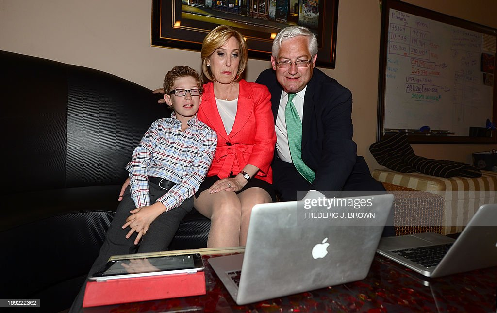 City Controller Wendy Greuel (C) follows election results online with her husband Dean and son Thomas Schramm after polls in a run-off election for Mayor closed in Los Angeles, California on May 21, 2013. Los Angeles councilman Eric Garcetti took a narrow lead in early results from a run-off election to succeed LA mayor Antonio Villaraigosa, but the race remained too close to call after midnight. Garcetti and Greuel, both Democrats like Villaraigosa, campaigned down to the wire after emerging from a March primary poll contested by a total of eight candidates. AFP PHOTO/Frederic J. BROWN