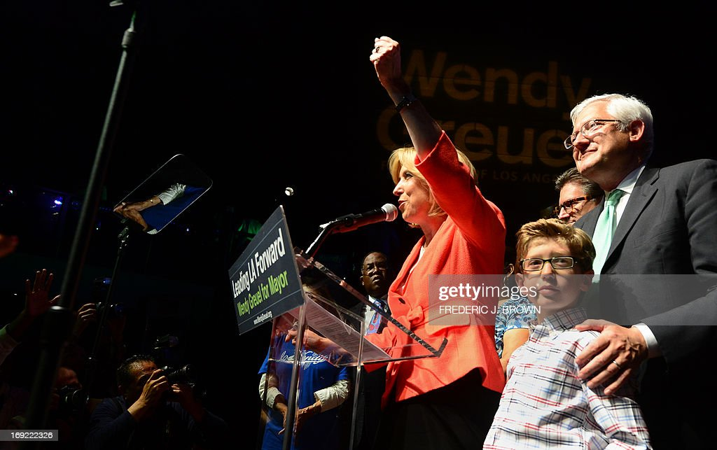 City Controller Wendy Greuel (C) gestures with her husband and son by her side as she meets her supporters after polls in a run-off election for Mayor closed in Los Angeles, California on May 21, 2013. Los Angeles councilman Eric Garcetti took a narrow lead in early results from a run-off election to succeed LA mayor Antonio Villaraigosa, but the race remained too close to call after midnight. Garcetti and Greuel, both Democrats like Villaraigosa, campaigned down to the wire after emerging from a March primary poll contested by a total of eight candidates. AFP PHOTO/Frederic J. BROWN