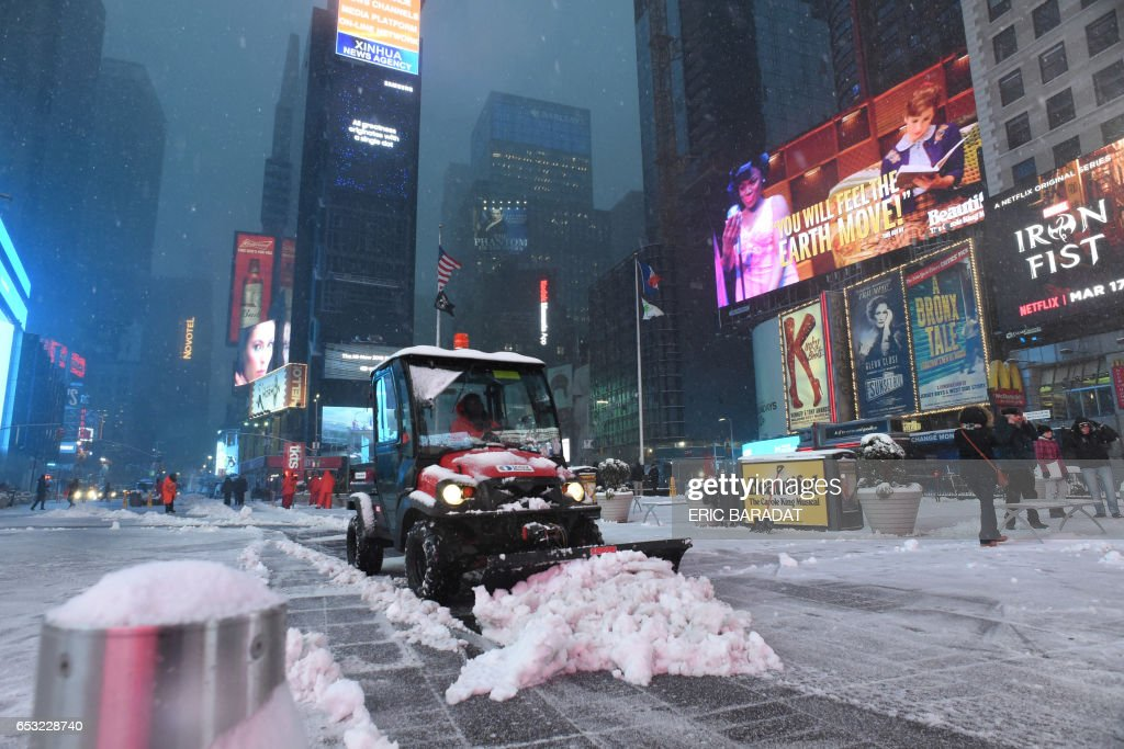 A city employee clears the sidewalk in Times Square during a snowstorm in New York on March 14, 2017. Winter Storm Stella dumped snow and sleet Tuesday across the northeastern United States where thousands of flights were canceled and schools closed, but appeared less severe than initially forecast. After daybreak the National Weather Service (NWS) revised down its predicted snow accumulation for the city of New York, saying that the storm had moved across the coast. PHOTO / Eric BARADAT