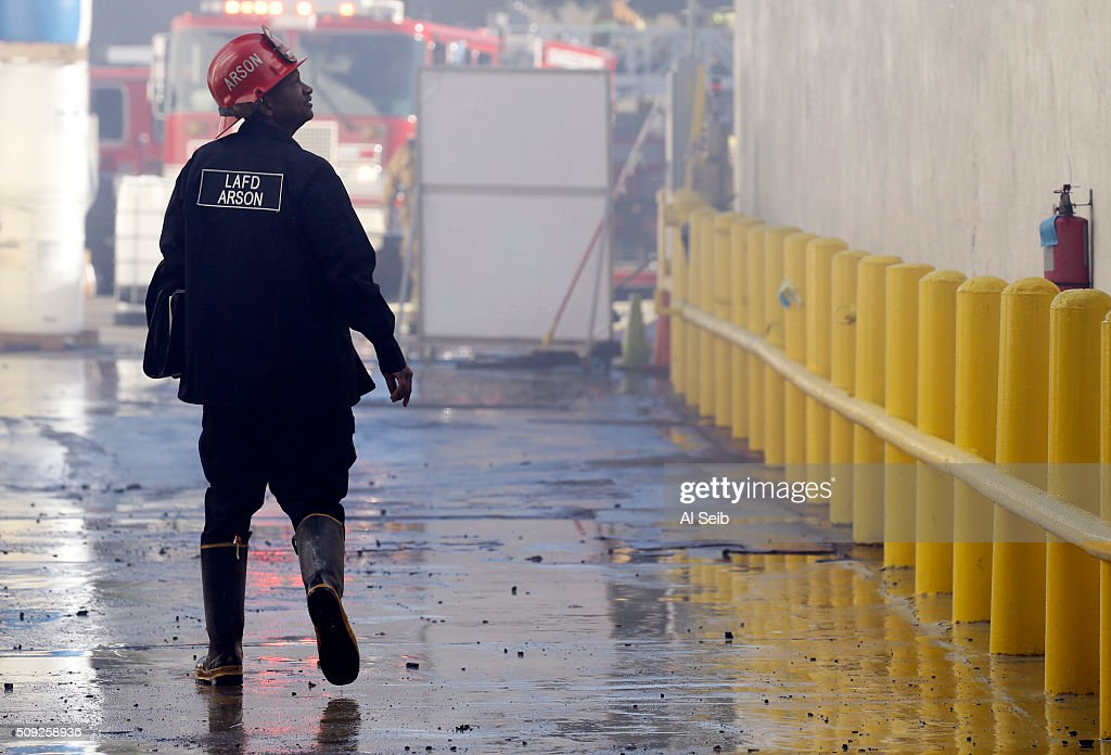 City Fire Arson investigators walk the scene as firefighters attack a fire in a small commercial building in the 1300 block of Newton Street near downtown Los Angeles Tuesday morning February 09, 2016. A firefighter fell and suffered minor injuries while battling the blaze.