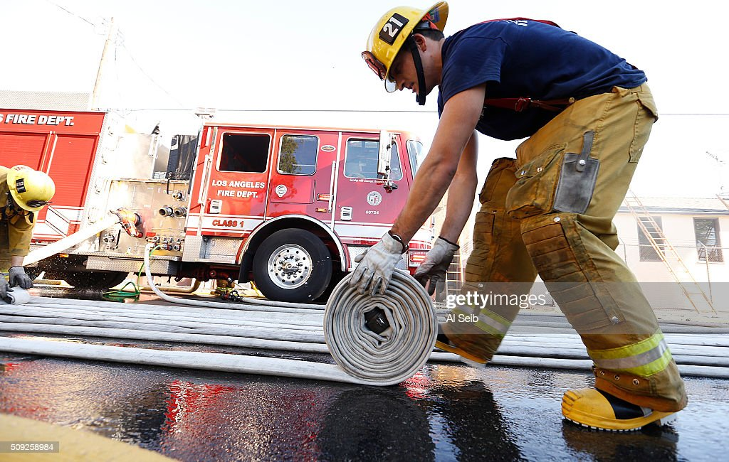 City Firefighter Abe Moreno rolls up hose after firefighters attacked a fire in a small commercial building in the 1300 block of Newton Street near downtown Los Angeles Tuesday morning February 09, 2016. A firefighter fell and suffered minor injuries while battling the blaze.