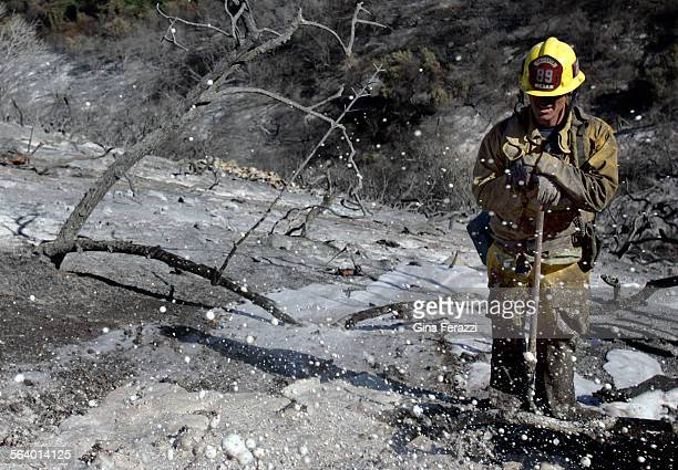 LA City firefighter Brian Stiers rests on his shovel in a sea of foam as firefighters still douse hotspots on scorched and rugged terrain on the east...