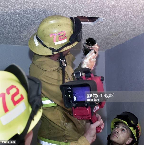 City firefighter Dwayne Kastor is shown freeing a trapped kitten the kitten from inside a ceilingThe kitten was located by firemen using a Bullard...