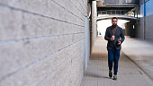 Young man with paper coffee cup walking on sidewalk towards the camera