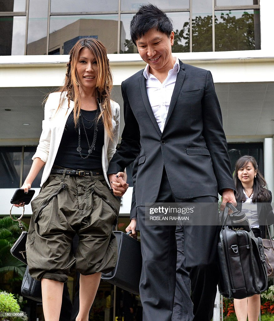 City Harvest Church founder Kong Hee (R) walks out for a lunch break with his pop-singer wife Ho Yeow Sun (L) during his trial at the subordinate courts in Singapore on September 9, 2013. The trial continues for the leaders of a Singapore-based Christian church accused of embezzling millions of dollars to finance the singing career of the pastor's wife.